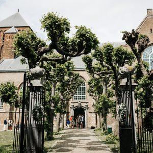 bruiloft dusty blue lambertuskerk raamsdonk wit wedding white decoratie zilveren trouwschoenen kransen hek versieren